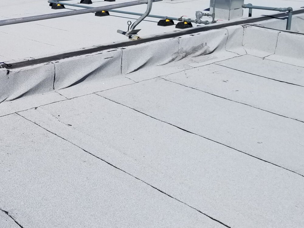 Image showing a commercial roof with wrinkles and deformations.
